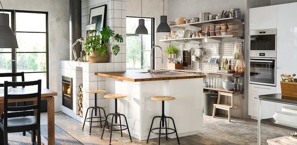 Ett vitt kök med en köksö i mitten med pallar runtomkring.