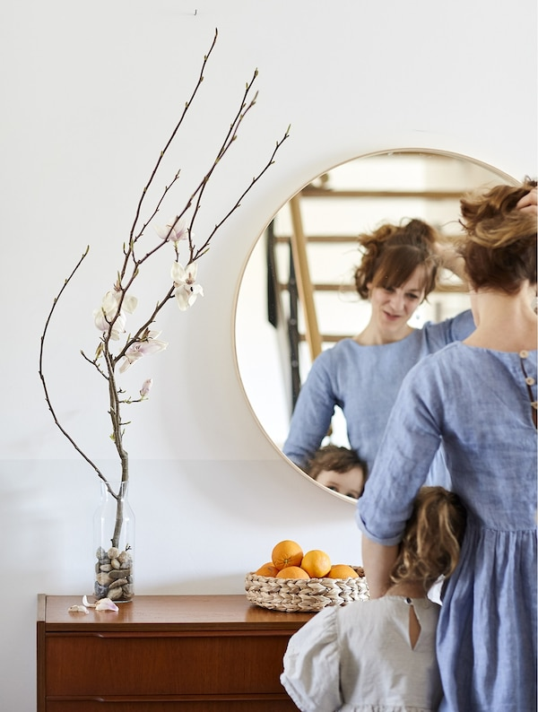 Eva and her daughter standing in front of a mirror and sideboard.