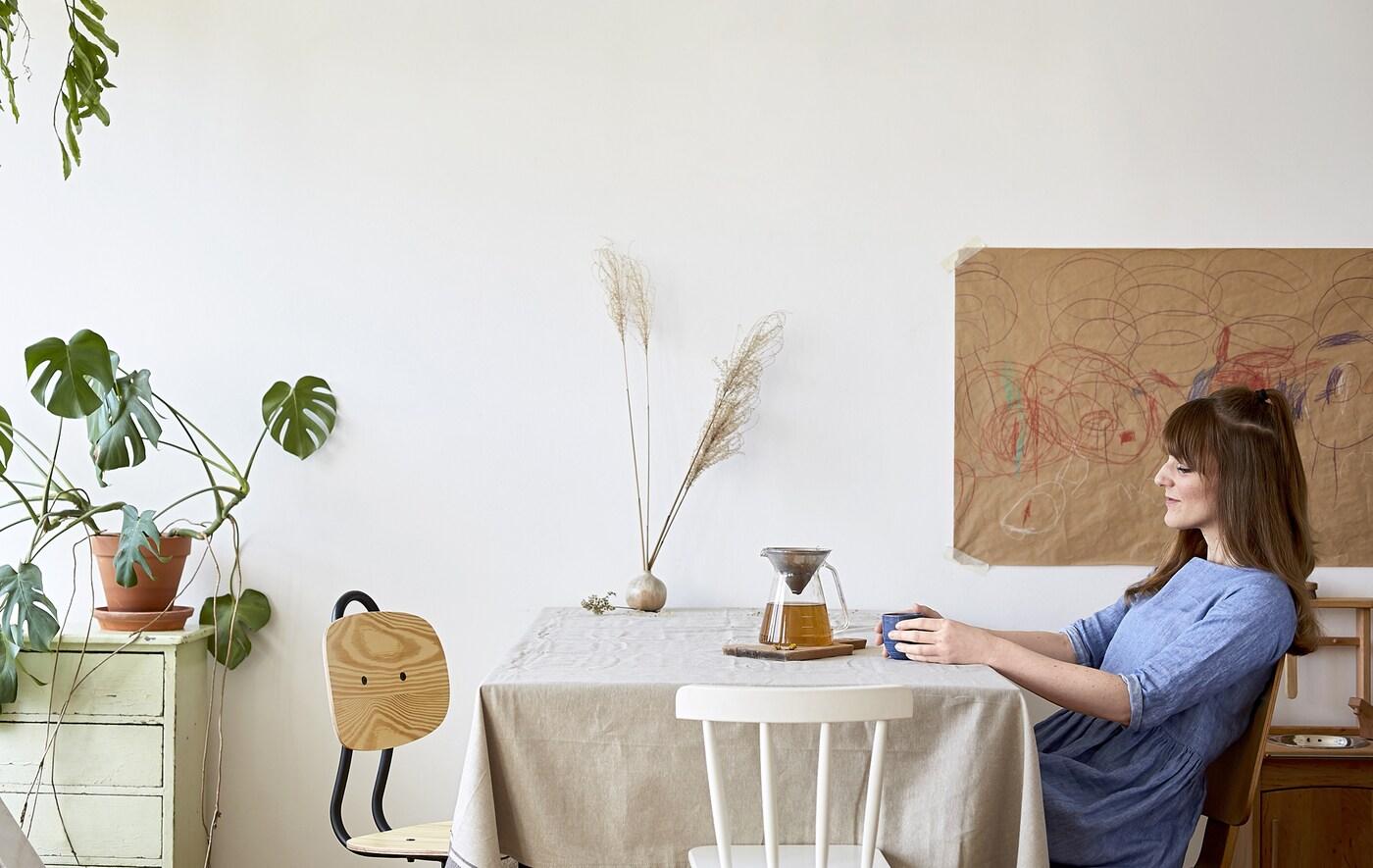 Eva assise à la table de la cuisine et buvant du thé dans une théière en verre.