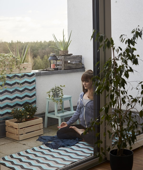 Eva practises yoga on a mat on the balcony with plants.