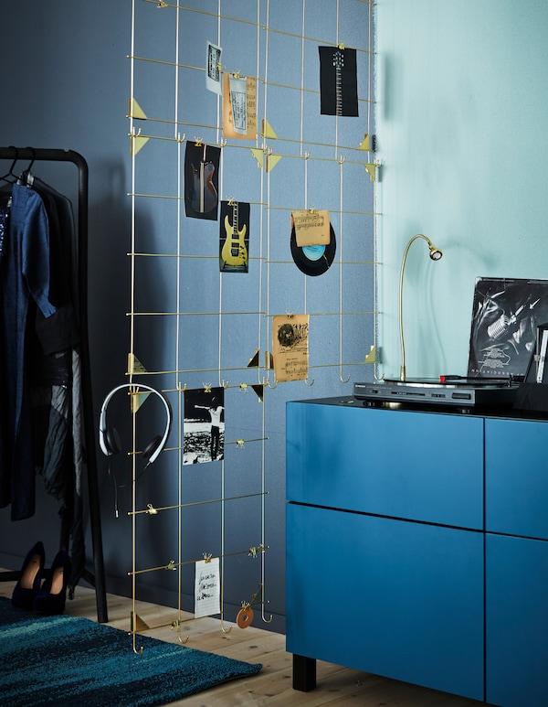Exposez vos objets préférés sur un séparateur de pièce versatile construit avec des cadres IKEA MYRHEDEN couleur laiton. Regroupez quatre cadres et attachez-les à un rail pour rideau fixé au plafond. Ensuite, accessoirisez!