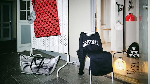 Exposició de la col·lecció limitada SAMMANKOPPLA en un rebedor il·luminat només pel flaix de la càmera i un dels llums amb cable.