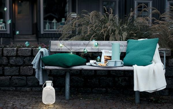 Extérieur, décor de début de soirée en ville avec un banc public aménagé avec un plateau à café, des coussins, un plaid et des éclairages décoratifs.