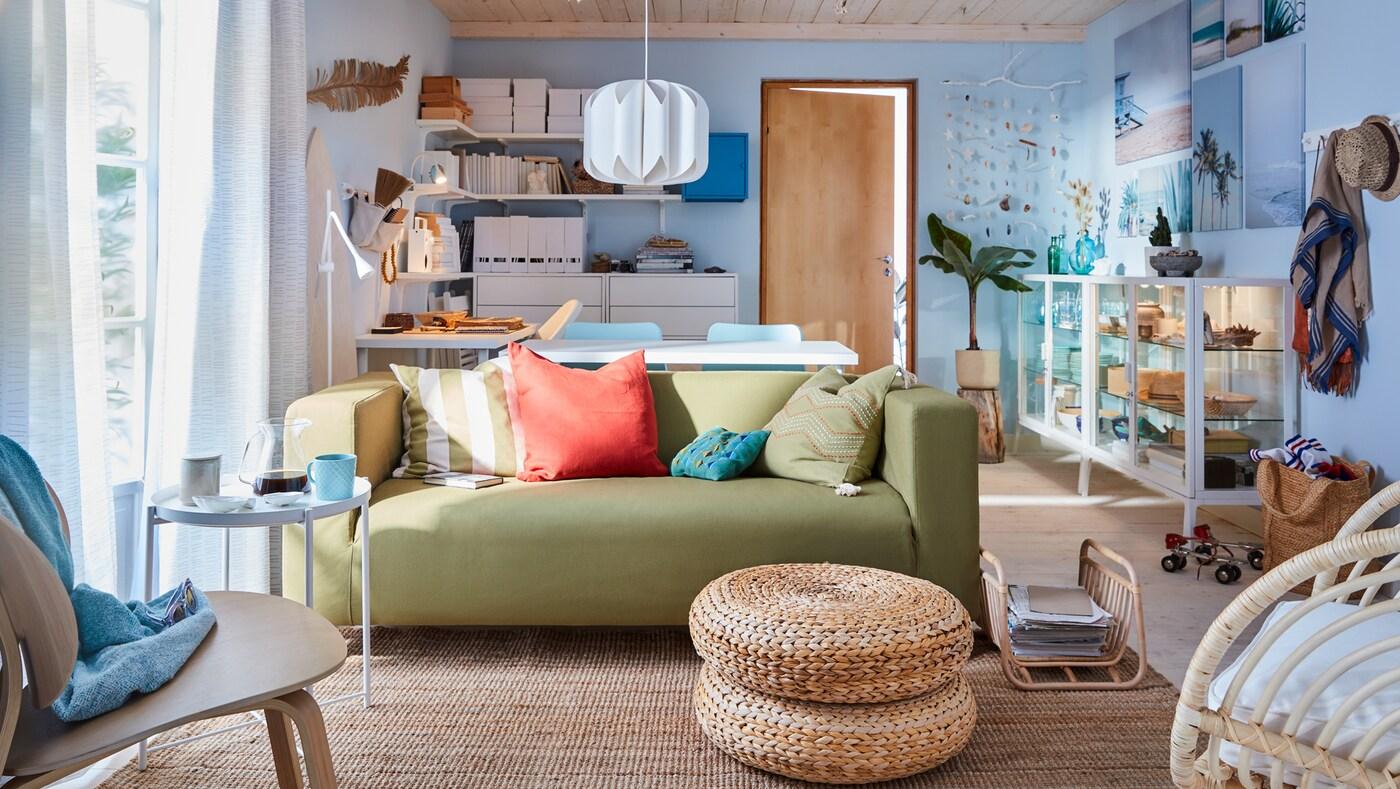 Ezt a nappalit a tengerpart ihlette: a falak világos kékek, a hatalmas jutaszőnyegen sárgászöld kanapé és fehér üvegajtós szekrények állnak.
