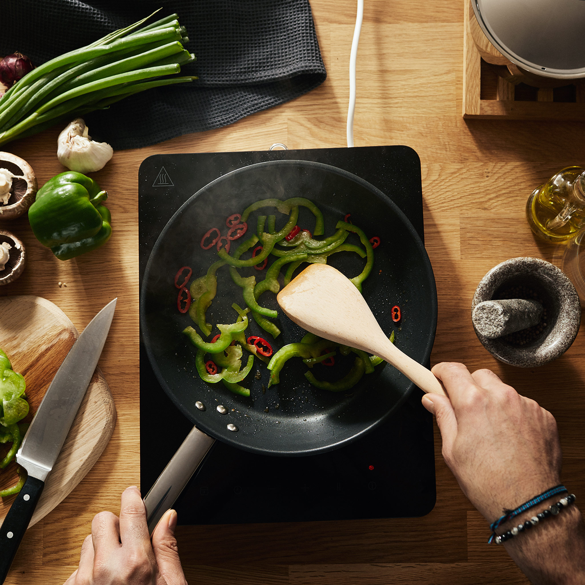 A man wearing bracelets preparing a vegetarian meal containing red and green peppers on a portable induction cooktop.