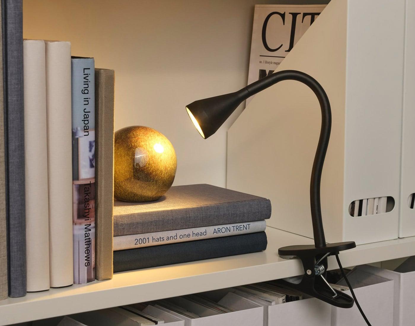 En sort klemspot lyser på en guldkugle på en hylde.