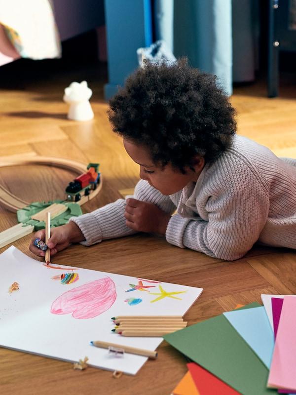 여러 장의 종이와 LILLABO 릴라보 기차놀이세트가 있는 바닥에 누워 MÅLA 몰라 연필과 MÅLA 몰라 도화지로 그림을 그리는 아이.