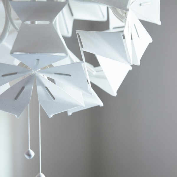 A close-up of RAMSELE pendant lamp made in a geometric shape that unfolds when the strings are pulled.