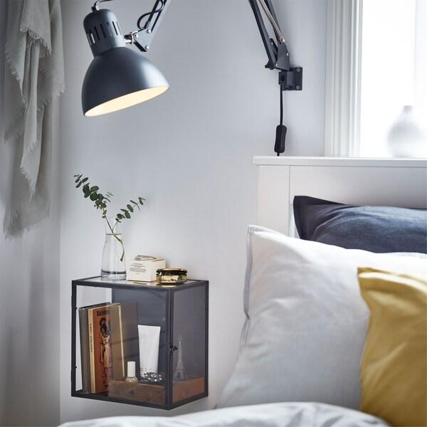 Tamnosiva IKEA TERTIAL radna lampa s prilagodljivom ručicom i BARKHYTTAN izložbena kutija pokraj uzglavlja kreveta.