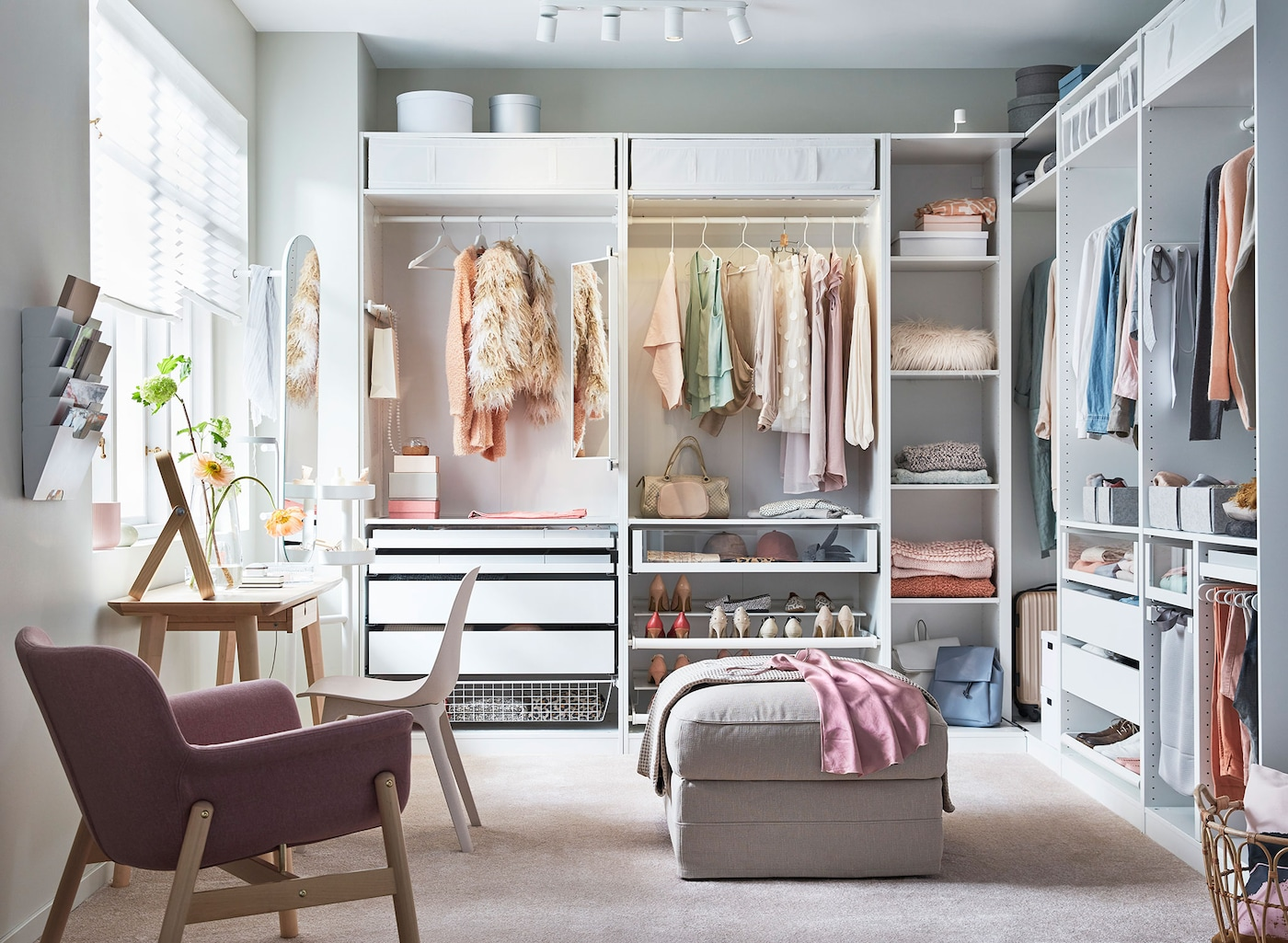 A large walk in closet with white cabinets featuring drawers, shelves and clothes hanging.
