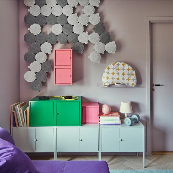 Paneles de insonorización ODDLAUG en gris sobre la pared de un pequeño salón con armarios, cajas y un sofá cama.