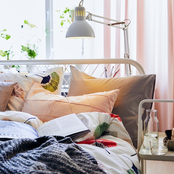 A white desk lamp hangs over a book and pillows on a bed.