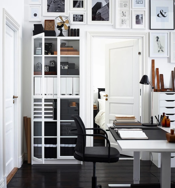 White adjustable desk lowered with tall, white bookcase with glass doors