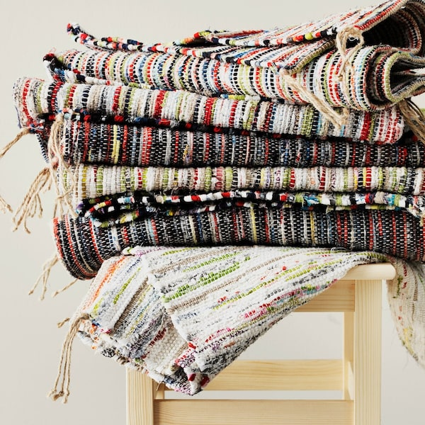 A pile of TÅNUM handmade rugs on a stool.