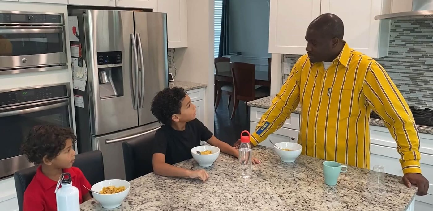 A man in yellow IKEA uniform standing talking to two young children around a kitchen countertop island.