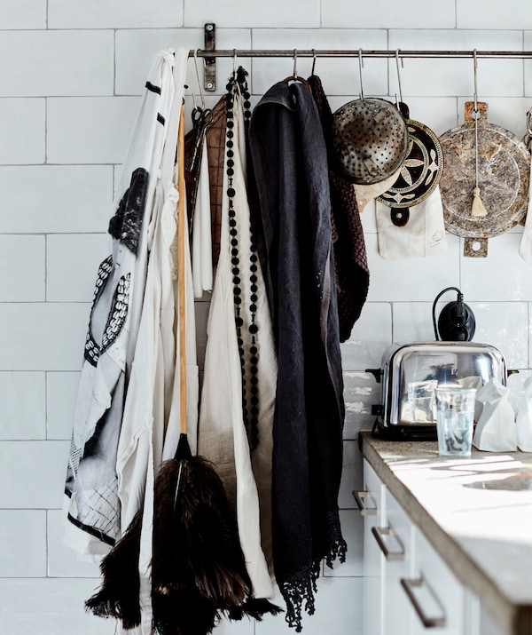 Fabric, a duster and colanders hanging on a metal rail on a white tiled wall.