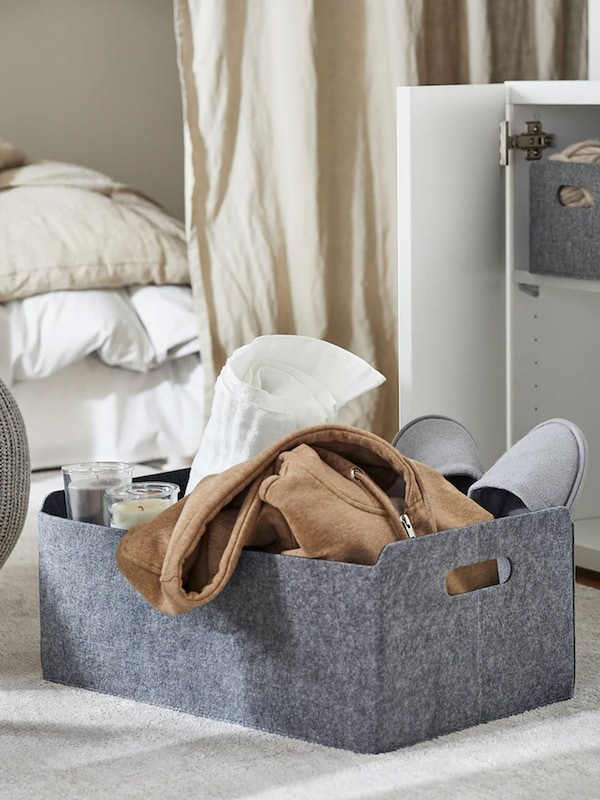 Fabric box sitting on floor with slippers, towel and robe stacked inside