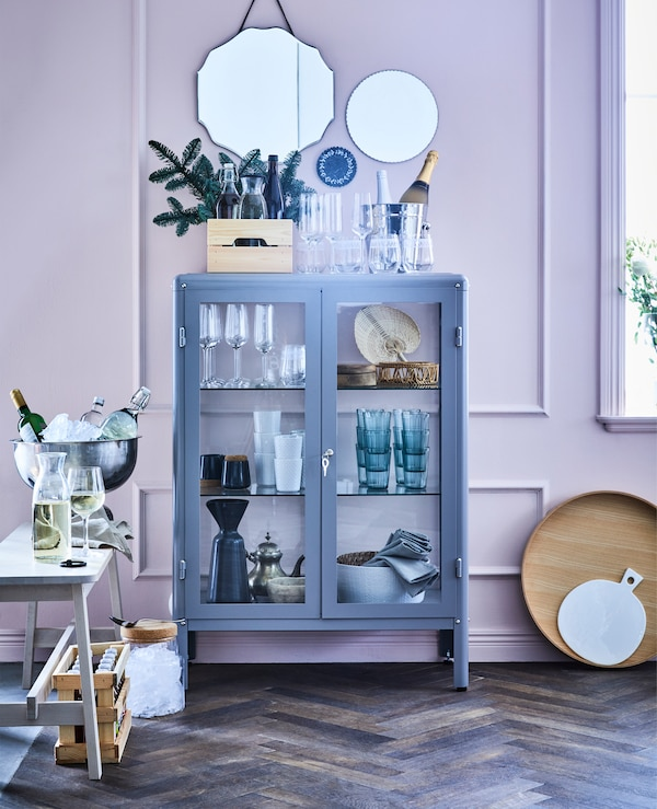 FABRIKÖR grey glass-door cabinet used as a bar cabinet filled with champagne glasses, drinking-glasses, tumblers and bottles.