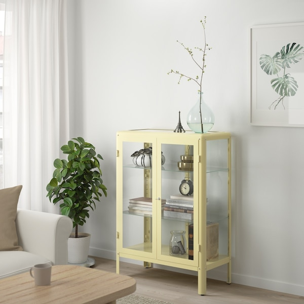 fabrikor vitrinekast in lichtgeel gevuld met accessoires in de woonkamer