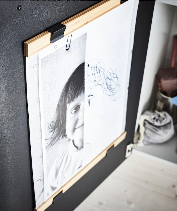 Face intérieure d'une porte d'armoire de cuisine, avec deux supports de poster – en haut et en bas – qui encadrent l'œuvre d'un jeune artiste.