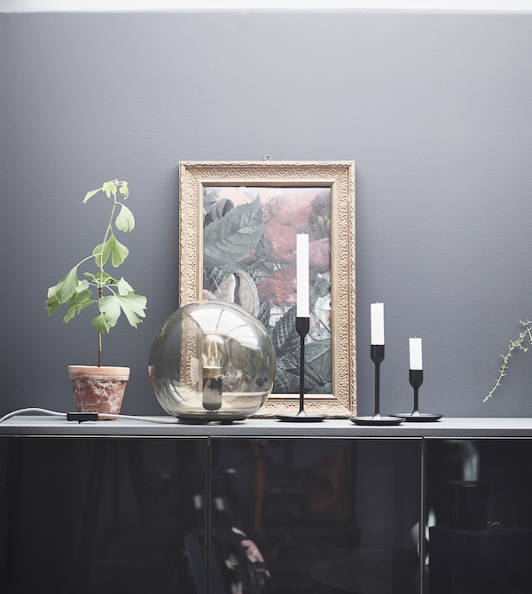 FADO table lamp on display with candles and a painting.