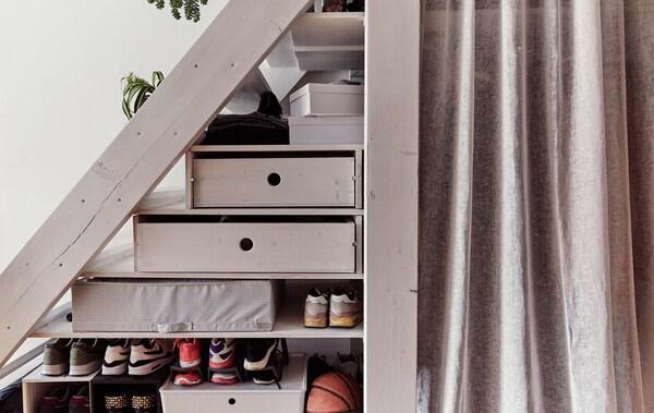 Fächer und Schuhe unter einer Treppe, u. a. mit Gardinenpaar.