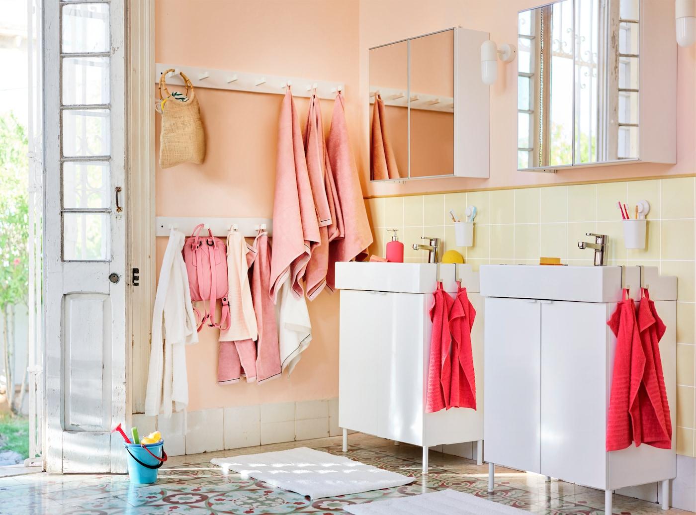 Färgglad badrumsmiljö med olika handdukar i både rosa och cerise, och väskor som hänger på väggen.