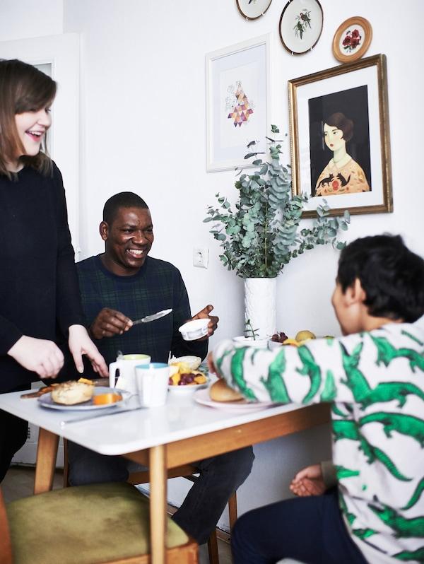 Familia de tres miembros en la mesa comiendo algo.