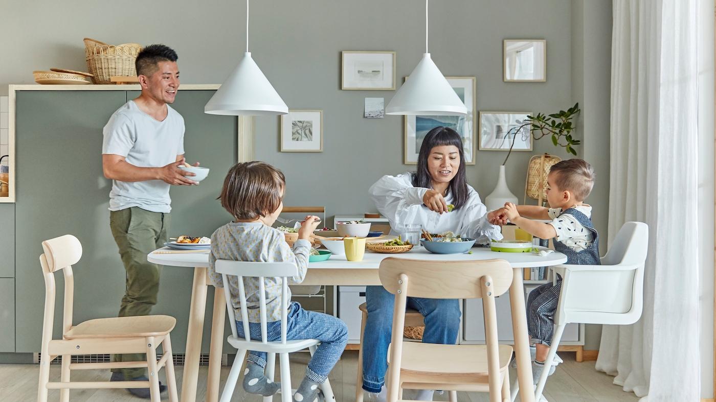 Familj på fyra personer som sitter vid köksbordet och äter.