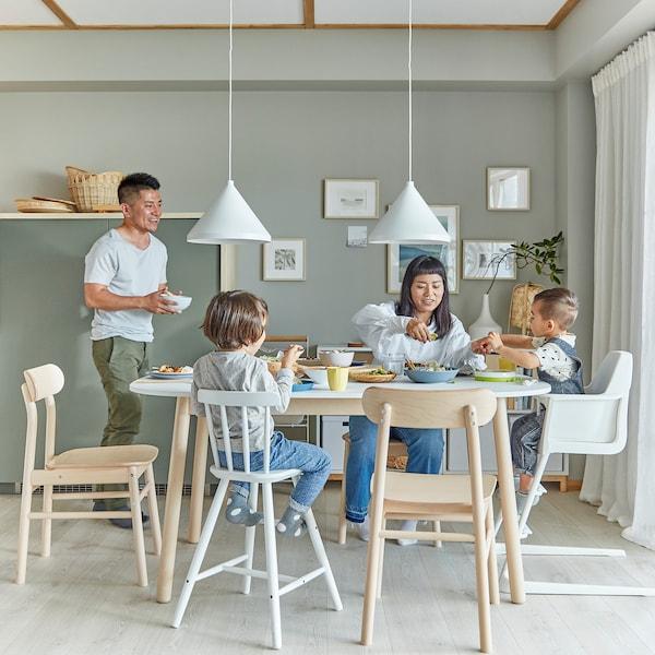Famille à la salle à manger La maman et les deux enfants sont assis à la table alors que le papa leur apporte un bol.