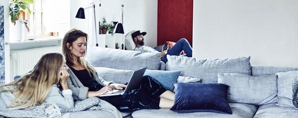 famille avec une mère et sa fille sur un canapé devant un ordinateuret leur père allongé dans le fond de la pièce avec son téléphone