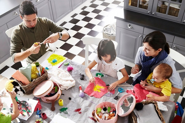 family of four sitting around their kitchen table doing arts and crafts