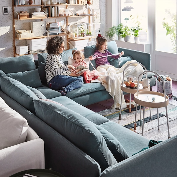 Family sat on  blue corner shaped SÖDERHAMN sofa, engaging in Knitting activities together.