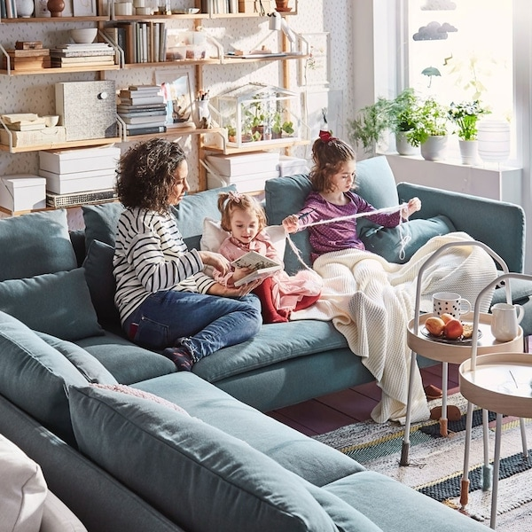 Family sat on blue corner shaped SÖDERHAMN sofa, engaging in Knitting activities together