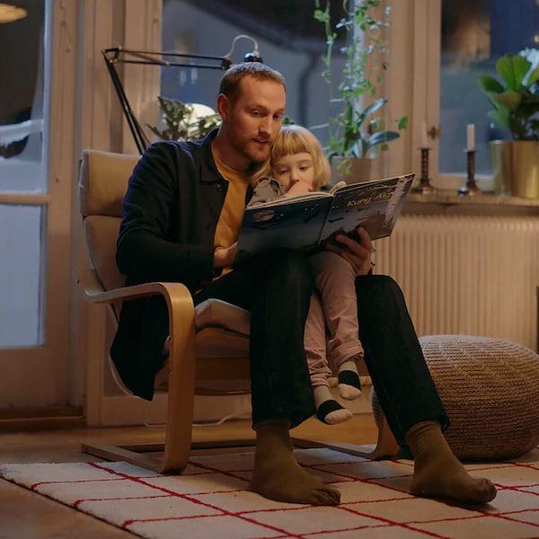 Far og datter som sitter og leser eventyr i en POÄNG stol som har vært med i generasjoner