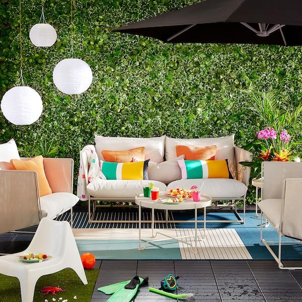 Farbenfroh gestaltete Terrasse mit bunten Kissen, Papierlaternen, Blumen & weißen Terrassensitzmöbeln.