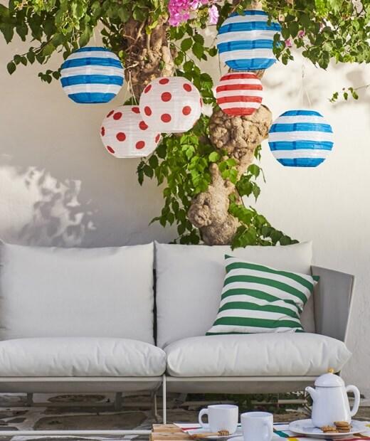 Farebné solárne lampáše IKEA SOLVINDEN zavesené na strome nad záhradnou pohovkou.