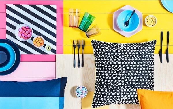 Farebný stôl s rozličným riadom, miskami so sladkosťami a vzorovanými vankúšmi.