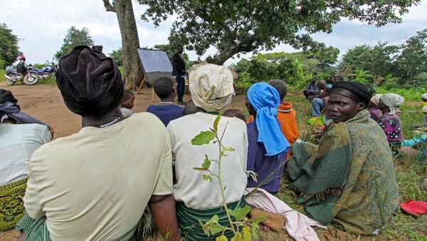 Farmáři v Ugandě sedící na zemi.