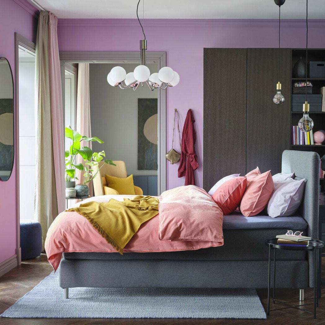 Farvestrålende soveværelse med lilla vægge, lys gammelrosa sengetøj, en gul plaid, et sortbrunt garderobeskab og en grå kontinentalseng.