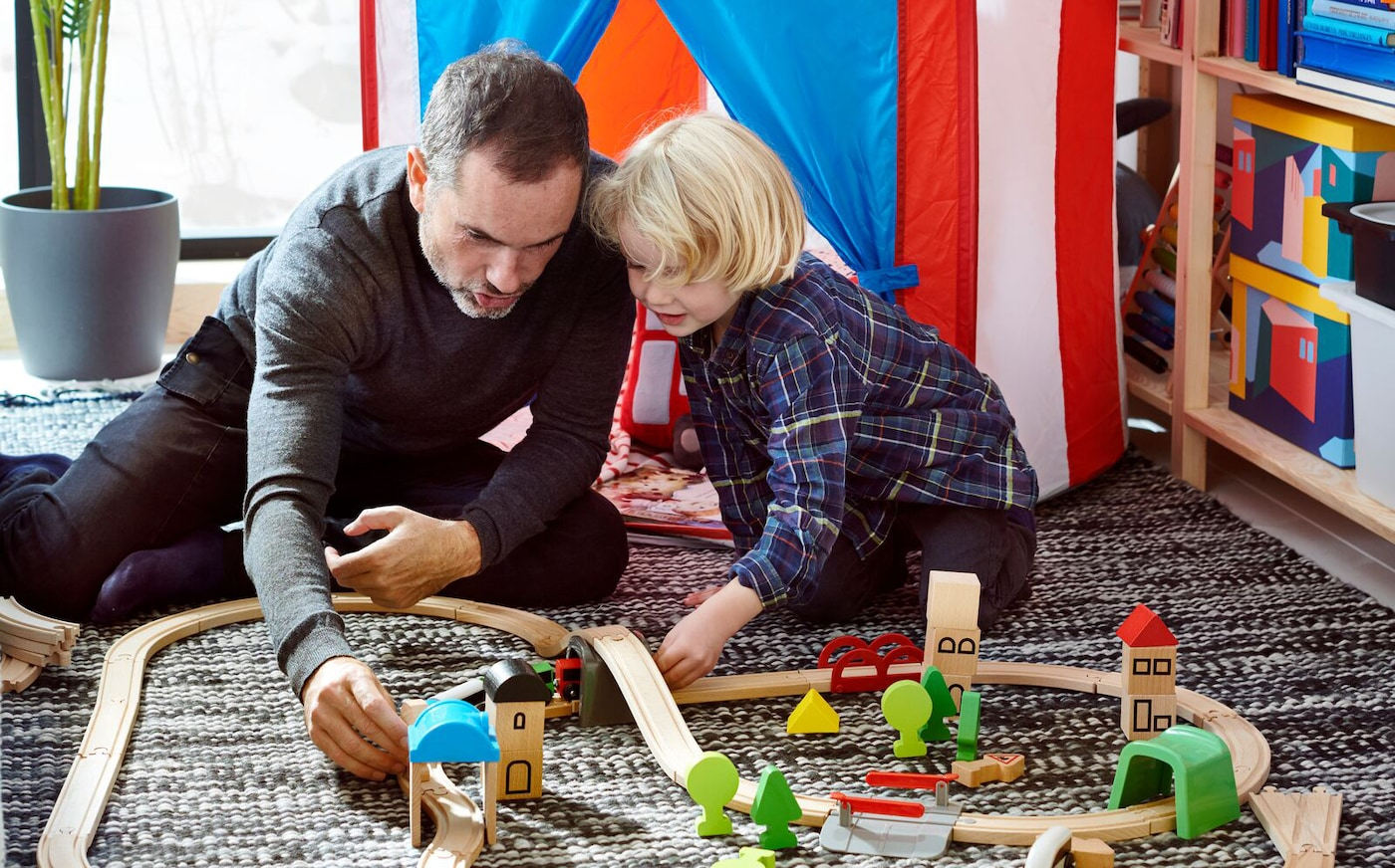 Father and child playing with LILLABO toy train set at home, with a striped play tent in the background.