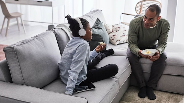 Father and daughter sitting on a KIVIK sofa