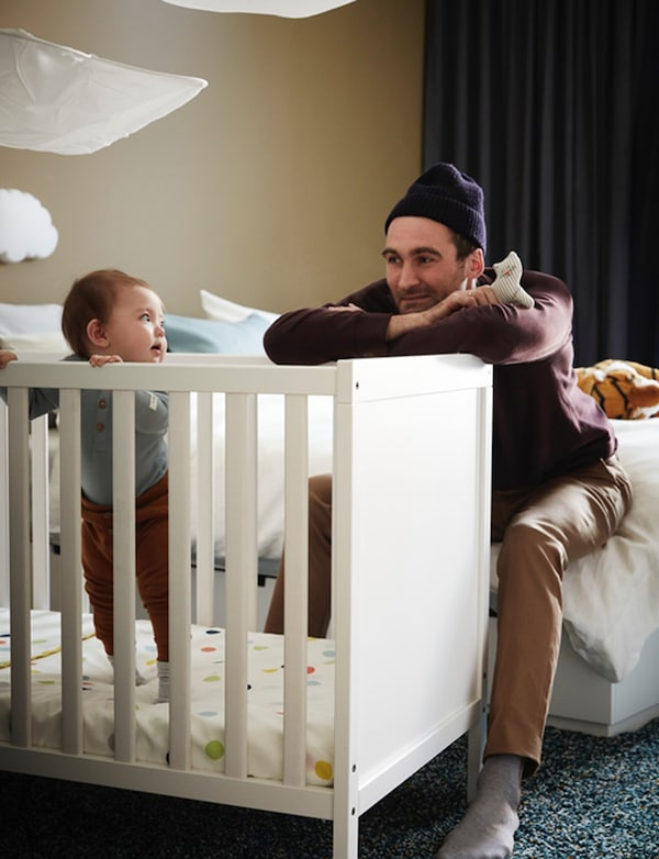 Father looking at son who is standing in an IKEA SUNDVIK crib with spotted bed sheet in a bedroom.