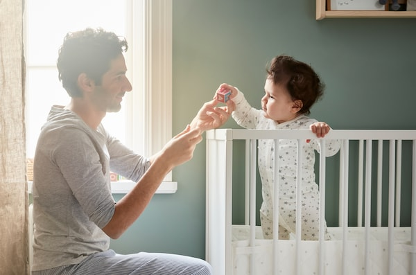 Father playing a game with his baby and a small wooden toy as the baby stands in a white cot holding on to the balustrade.