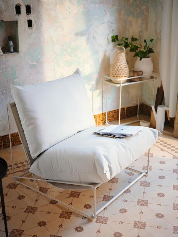 Fauteuil blanc posé sur un sol en carrelage à motifs.  Quelques magazines sont disposés sur le fauteuil.