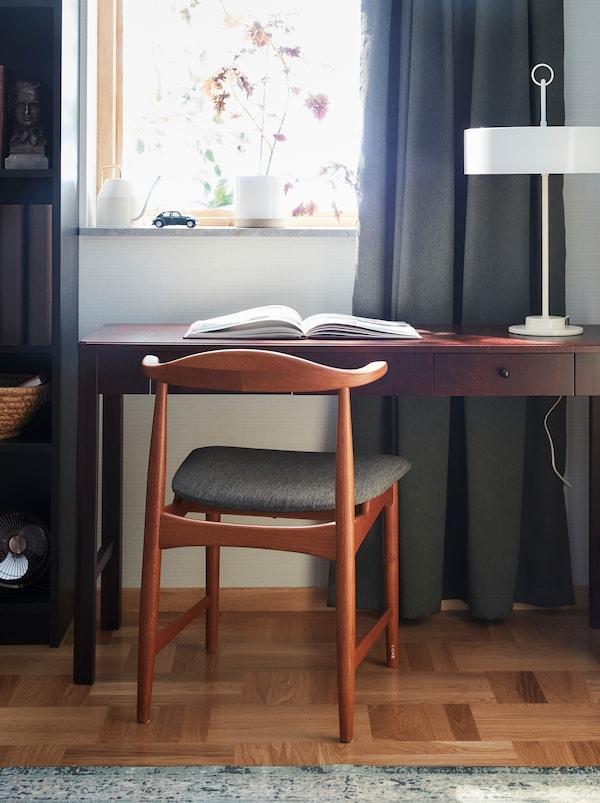 Fauteuil DANSKE en chêne et son assise en tissu conçu pour IKEA dans les années60 placé devant un bureau en boisfoncé.