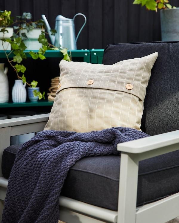 Fauteuil d'extérieur gris avec coussins d'assise et de dossier en gris foncé, coussin d'extérieur beige et plaid gris foncé.