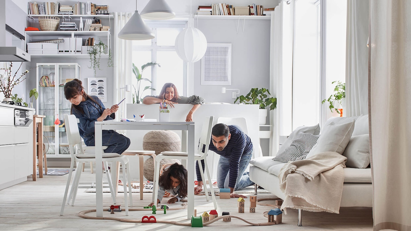A family in a dining room with white home furnishings and toys.