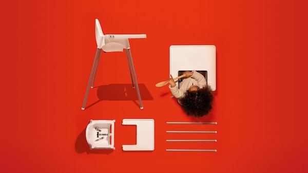 Fehér etetőszék, a tálca fölött egy kisgyerek egy kanállal játszik, mellette a földön egy másik etetőszék darabjai sorban elrendezve. ther chair on a red background.
