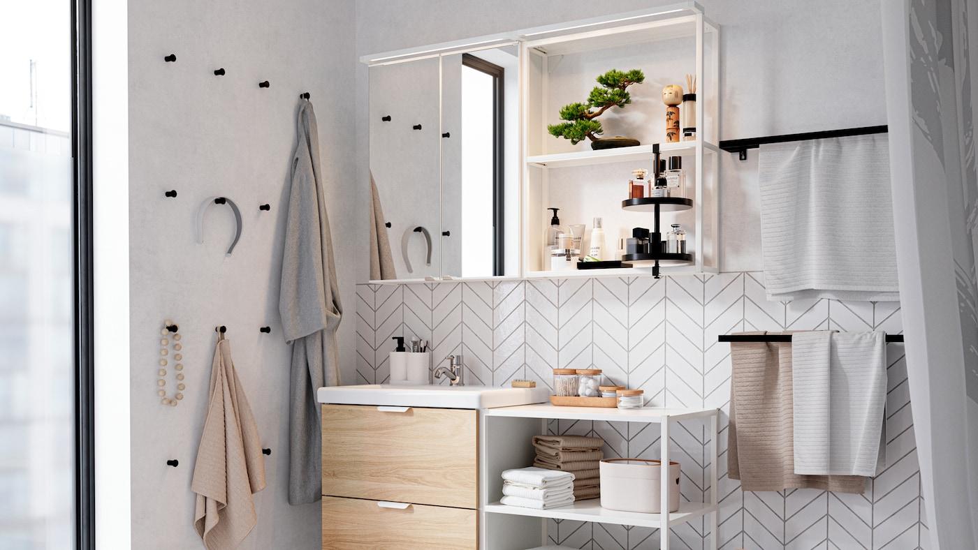 Fehér fürdőszoba-garnitúra, fekete akasztók a falon, a nyitott tárolón törülközők, parfüm, egy bonsai fa és egy fürdőköpeny.